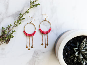 Top view of Dangly stars style macrame earrings in pink color Made with knotted waxed polyester and brass components.
