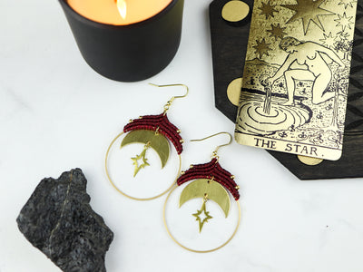 Top view of moon and star macrame hoop earrings in red.
