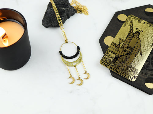 Top view of moon phase with dangly mini moon macrame necklace in black and gold