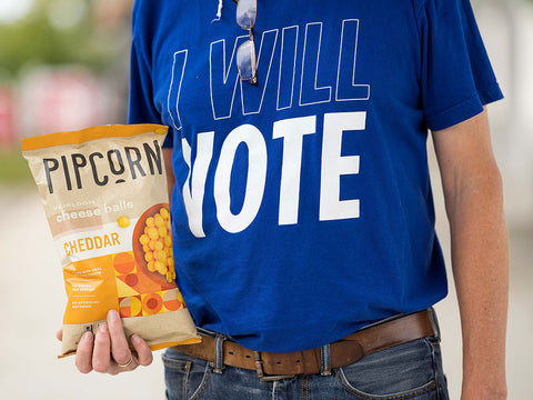 Voter holding Pipcorn Cheese Balls