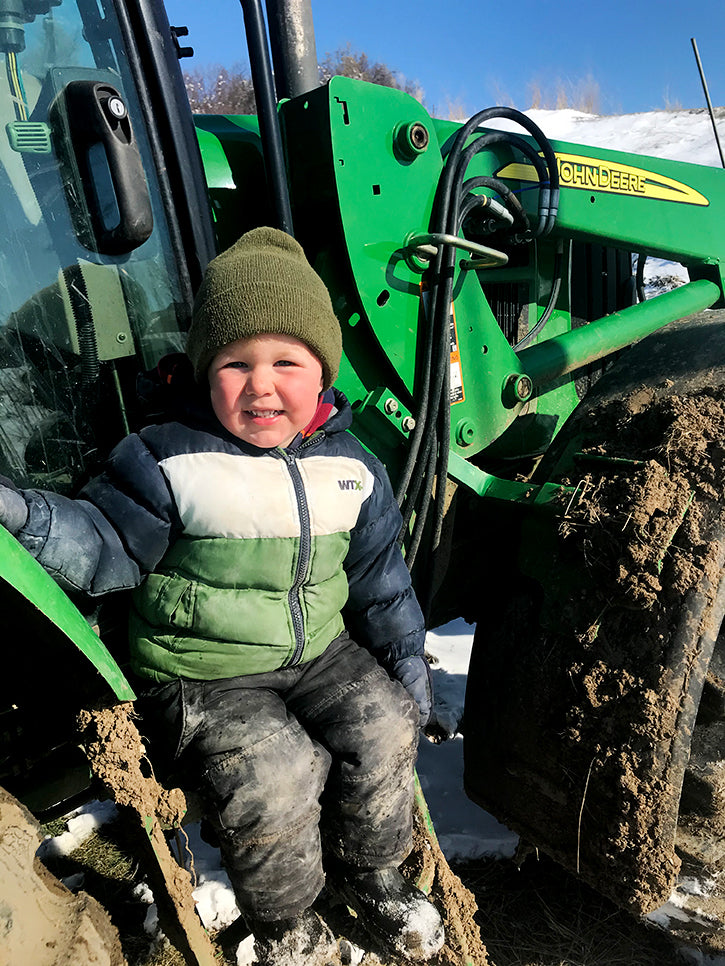 barett on tractor in his winter coat and hat