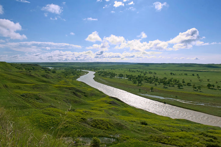 cheyenne river with blue skies and green prairie