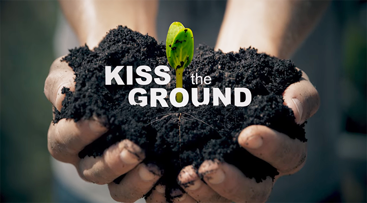screenshot of hands holding dark soil with title kiss the ground