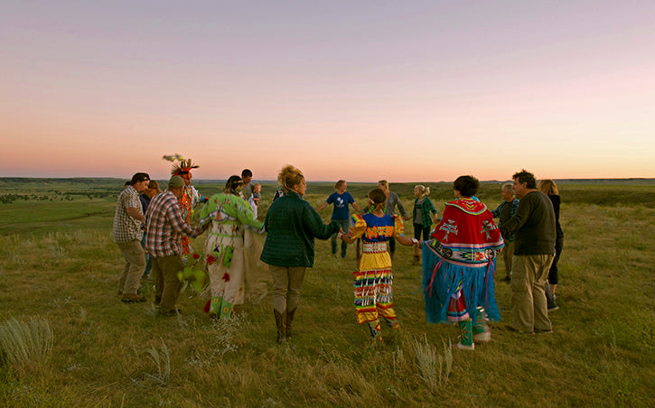 pow wow on grasslands with sun setting