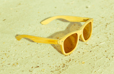 light shaded wood sunglasses on the sand
