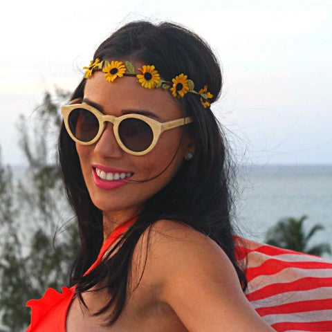 girl with floral head band wearing wooden sunglasses