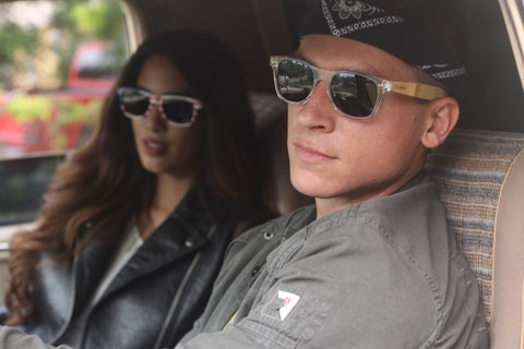 girl and boy in leather jacket and sunglasses chillin inside a car