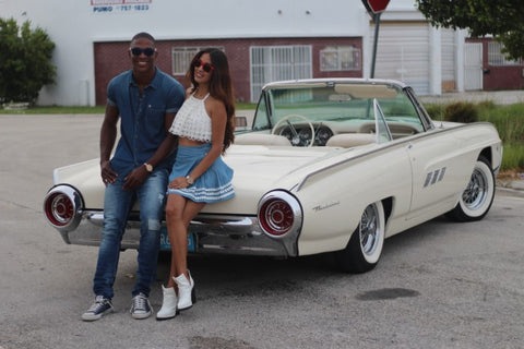 couple cillin' on the hood of their vintage white convertible car