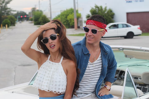 couple in sunglasses chilling on their white convertible car
