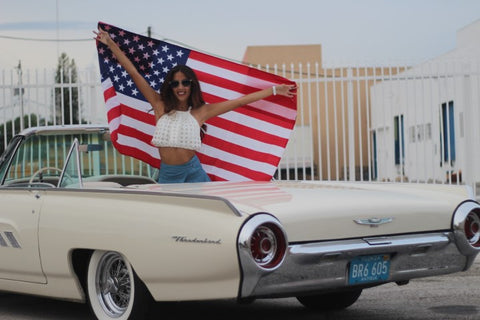 girl hold a US flag in a white convertible car