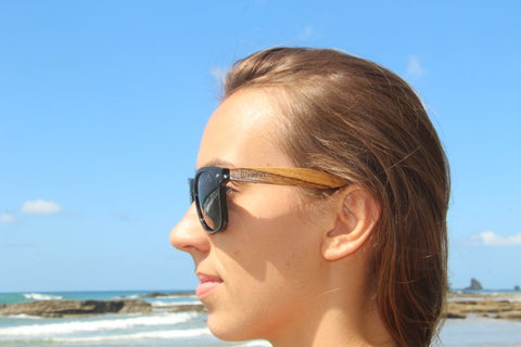 girl in the beach wearing wooden sunglasses