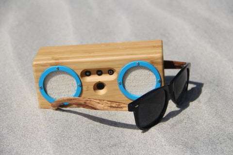 wooden speaker and wooden sunglasses on the sand