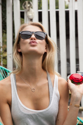 blonde girl in white tank top wearing sunglasses blowing a kiss