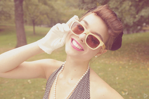 girl posing with white glove and wooden sunglasses