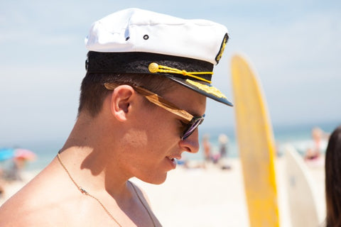 captain in wooden sunglasses at the beach