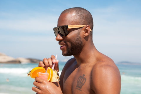 guy in the beach enjoying his drink