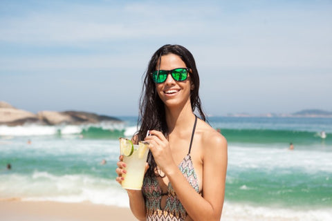 girl  wearing sunglasses at the beach drinking