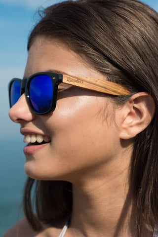 girl with long hair wearing a wooden blue shade sunglasses