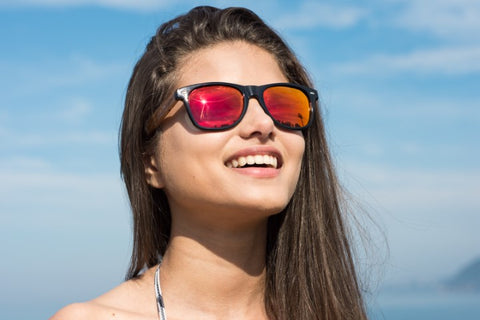 girl with long black hair wearing a wooden red orange shade sunglasses