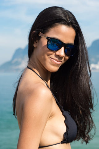 girl with long black hair in black bikini wearing a wooden blue shade sunglasses