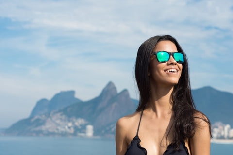 girl with long black hair in black bikini wearing a wooden bluish green sunglasses