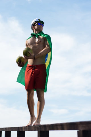 guy in captain's hat wearing blue sunglasses and a flag of Brazil as a cape holding 2 coconut