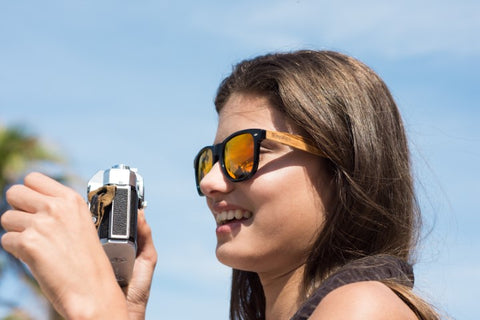 girl with long hair wearing wooden sunglasses in the shade of red orange taking a picture of something