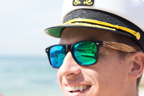 guy in captain's hat wearing wooden sunglasses in the shade of bluish green with the brand of woodies