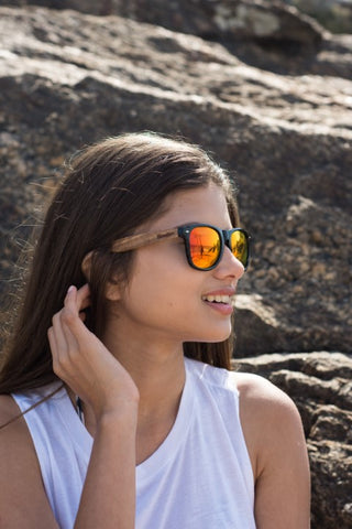 girl with long hair in white top wearing wooden sunglasses in the shade of orange