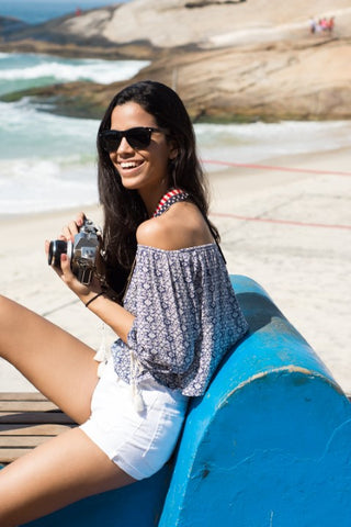 girl with long black hair wearing wooden sunglasses in the shade of black holding a camera