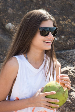 girl with long brown hair wearing wooden sunglasses in the shade of black drinking from a coconut