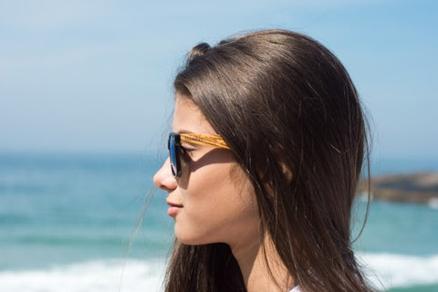 girl with long black hair wearing wooden sunglasses with the brand woodies