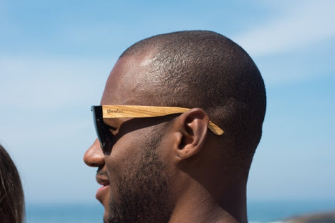 guy wearing wooden sunglasses in the shade of black with the brand woodies