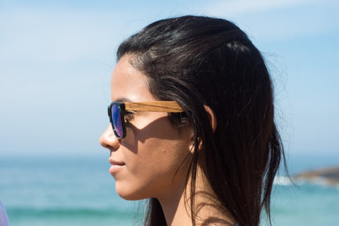 girl with long black hair wearing wooden sunglasses in the shade of blue with the brand woodies