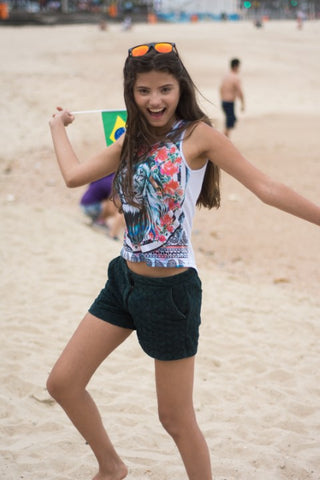 girl in the beach wearing tank top and short holding a flag of Brazil with orange sunglasses on her head