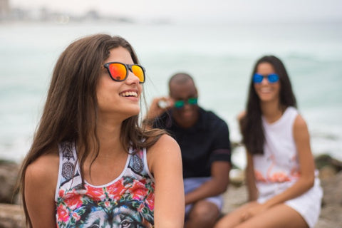 girl in tank top wearing a sunglasses in the shade of red orange with her friends behind her