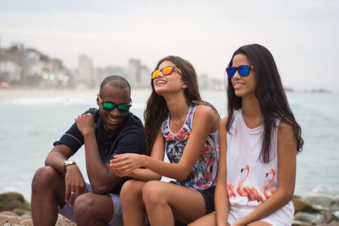 1 guy and 2 girls hanging out all wearing wooden sunglasess in the shade of green orange and blue