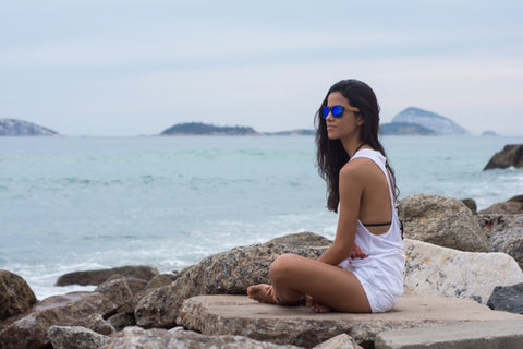girl in white tank top sitting on the rocks wearing wooden sunglasses in the shade of blue