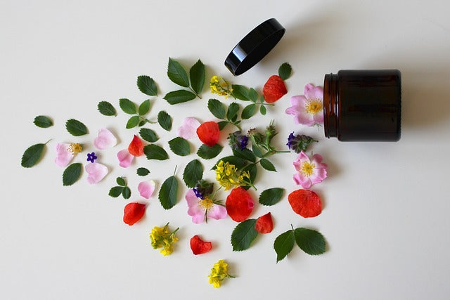 flowers, leaves and petals spilling out of a skincare tub