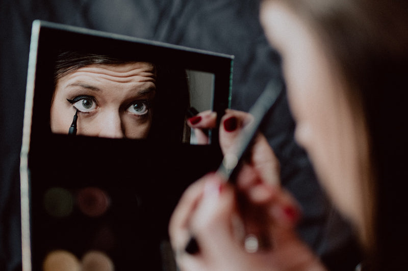 A woman applying black eyeliner in a compact mirror