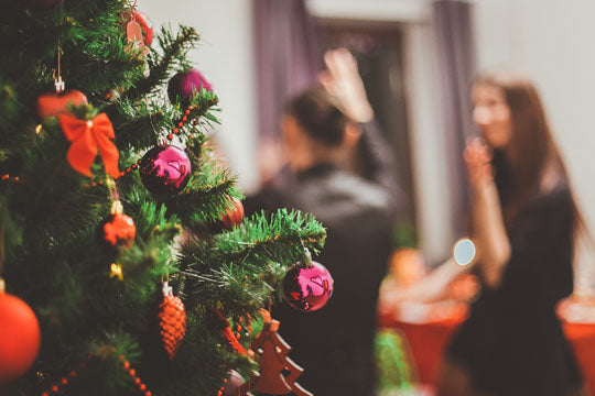 People at a Christmas party reception with a Christmas tree in the foreground