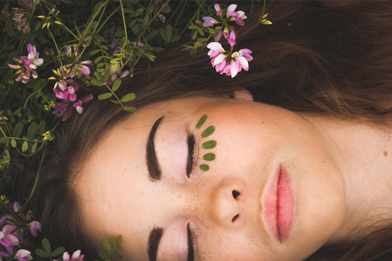 Woman lay in grass and flowers with glowing skin that is a result of cleansing and toning your face