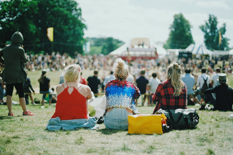 demonstrating festival tips for first timers, three women are sitting on grass overlooking the crowd.