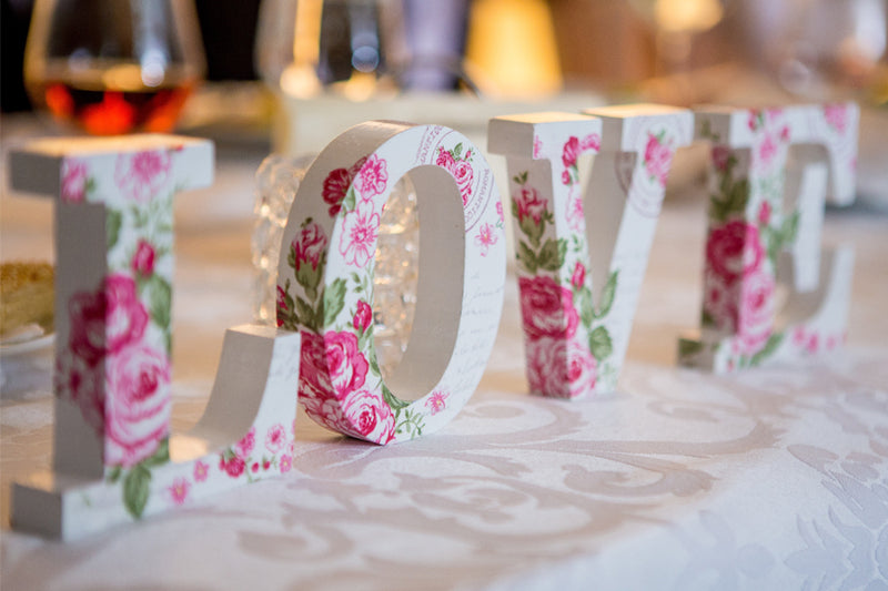 Looking for fun wedding reception ideas? Floral love sign used as decoration on table