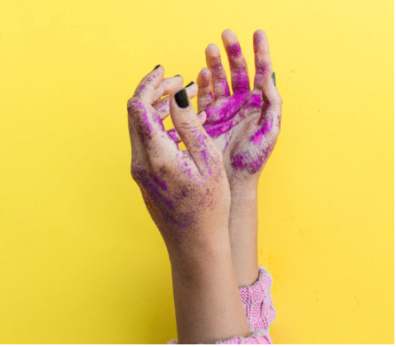 is glitter safe? pink glitter on hands and a yellow background
