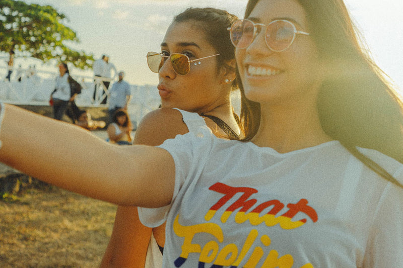 two girls at a festival demonstrating tips for taking a selfie