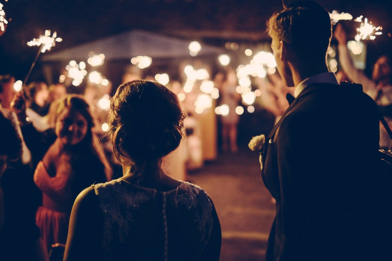 A bride and groom surrounded by sparklers as an alternative wedding entertainment ideas
