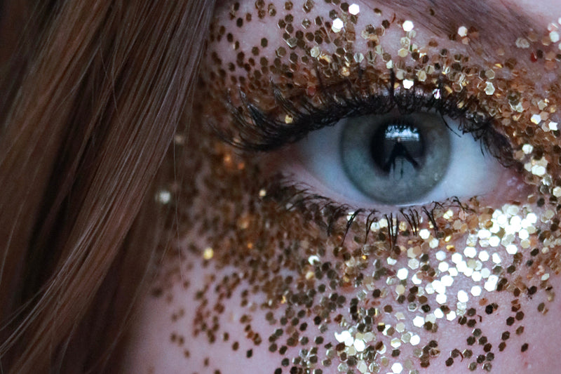 Close up of a woman wearing guilt free glitter around her eye as makeup