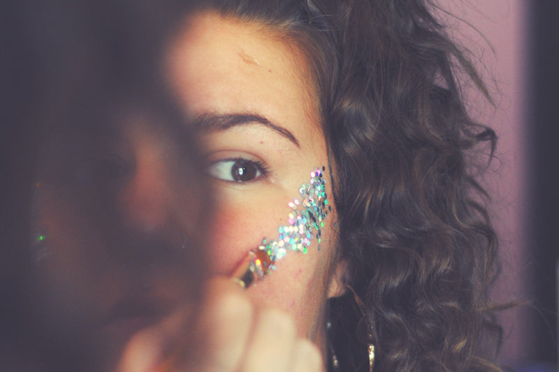 Girl applying glitter to her face, which is on the the must have festival beauty products