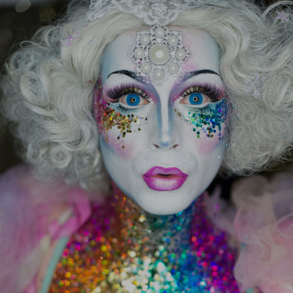 face glitter in rainbow colours worn by a woman in a white wig and pink dress